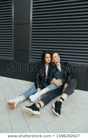 Photo of two caucasian girls wearing casual clothes sitting on g Stock photo © deandrobot