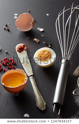 Raw and boiled egg, a metal whisk and a knife with red pepper on a black concrete background. Prepar Stock photo © artjazz