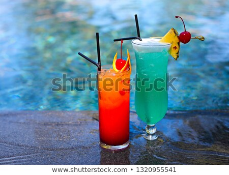 Glass with a bright blue lagoon cocktail by the pool Stock photo © dashapetrenko