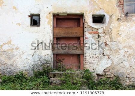 Broken window with two boards nailed on it stock photo © colematt