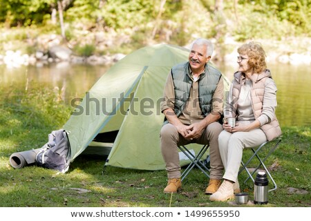 Happy mature active spouses discussing moments of their trip by tent Stock photo © pressmaster