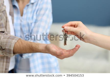Female hand giving a key to the house man's on background of wooden door. Owning real estate concept Stock photo © galitskaya