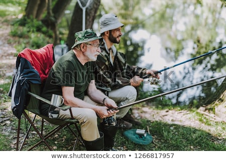 friends with fishing rods and net at lake or river Stock photo © dolgachov