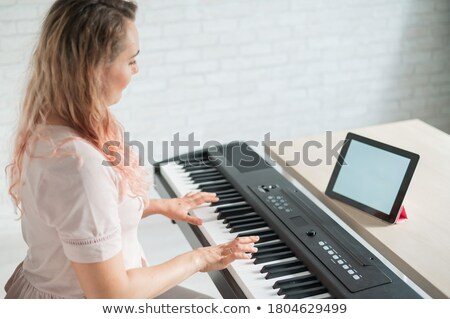 Learning to play on a digital synthesizer  Stock photo © krugloff