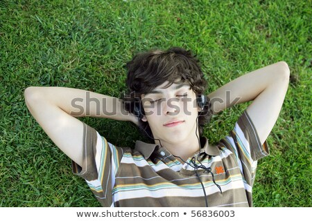 Portrait of a boy listening to music with headphones laid on the grass Stock photo © photography33