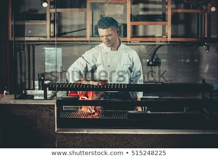 Happy young chef cooking steak in the oven  Stock photo © dacasdo