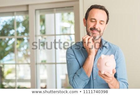 Middle aged man saving money in piggy bank Stock photo © ozgur