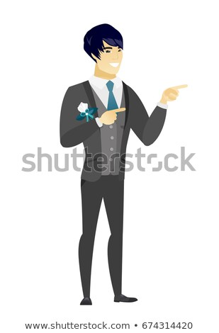 Young asian fiance pointing to the side. Stock photo © RAStudio