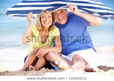 Couple sheltering under beach parasol Stock photo © IS2