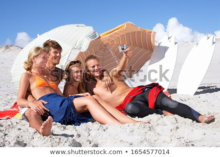 Four hugging girlfriends at the beach. stock photo © Massonforstock