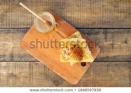 Honeycomb on old wooden cutting board Stock photo © Melnyk