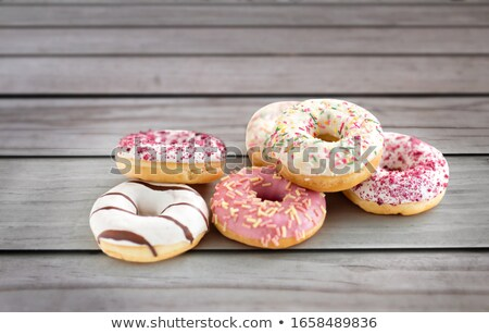 close up of glazed donuts pile on wooden board Stock photo © dolgachov