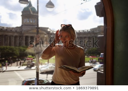 A girl stands on the street against the background of a street cafeteria in a blurred background Stock photo © ElenaBatkova