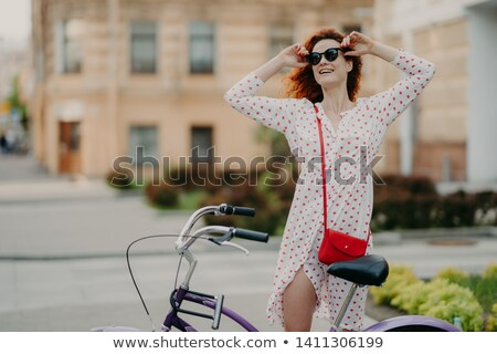 Happy carefree woman cycles in city, poses near bicycle, keeps hands on shades, dressed in white dre Stock photo © vkstudio