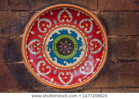 Balinese decoration, painted plate on a stone wall Stock photo © galitskaya