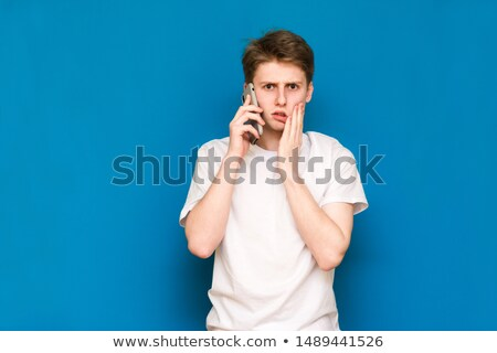 Thoughtful handsome young man in t-shirt, holding smartphone near ear, having conversation, touch ch Stock photo © benzoix
