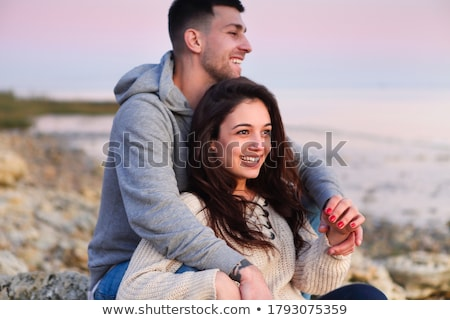 Young couple at rocky seacoast in sunset Stock photo © dashapetrenko