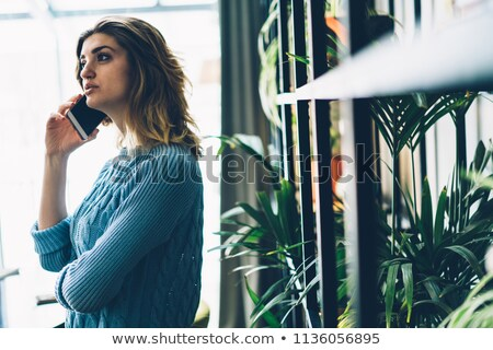 Concentrated pretty young girl near shelf using mobile phone. Stock photo © deandrobot