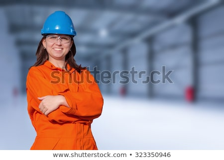 Woman wearing blue work overalls and hard hat Stock photo © photography33