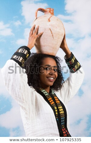 Attractive young african woman carrying jug with water Stock photo © HASLOO