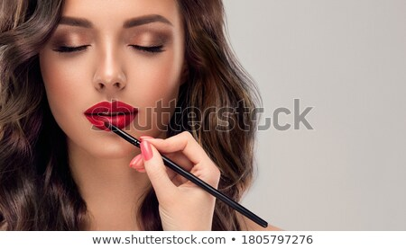 Which girl of a lip paints visagiste with red  lipstick Stock photo © fanfo