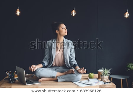 Stock photo: Business woman meditating in lotus pose.