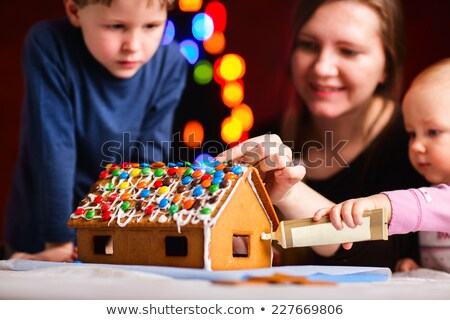 mother boy decorating gingerbread house stock photo © is2