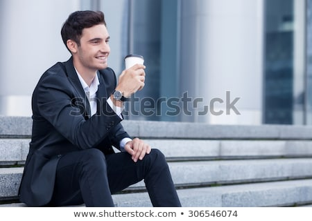 Stock photo: Happy young man sitting on steps outdoors looking aside holding phone.