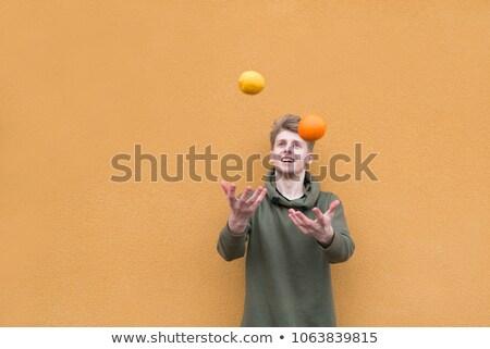 Jonge man jongleren vers sinaasappelen portret glimlachend Stockfoto © Kzenon
