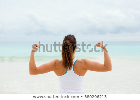 Sports woman showing biceps outdoors on the beach. Stock photo © deandrobot