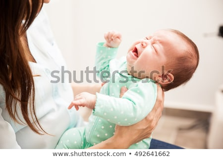 Mother trying to calm her crying baby Stock photo © Lopolo