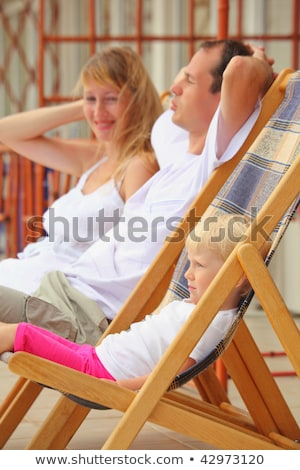 Happy family with little girl reclining on chaise lounges on ver Stock photo © Paha_L