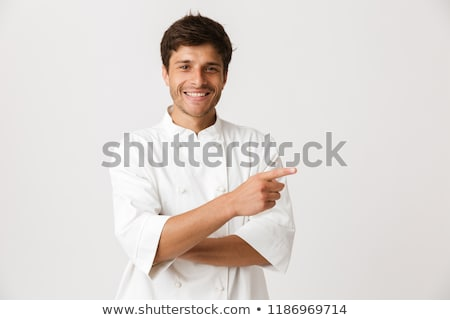young chef man standing isolated over white wall background holding crockery stock photo © deandrobot