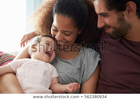 parent with baby daughter on sofa at home stock photo © lopolo