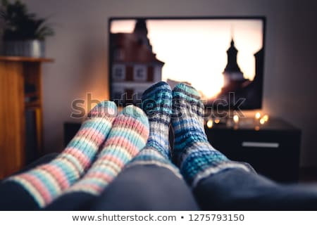 Couple watching tv at home sitting in a comfortable couch in the livingroom at home Stock photo © Lopolo