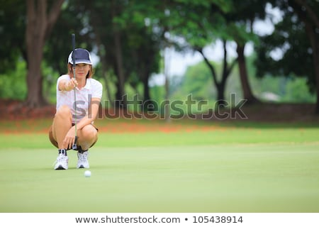 Female golfer concentrating on putting Stock photo © lichtmeister
