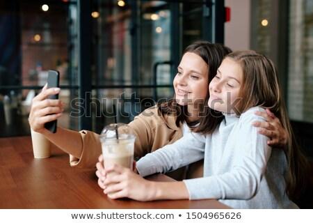 Affettuoso madre figlia bevande guardando smartphone Foto d'archivio © pressmaster