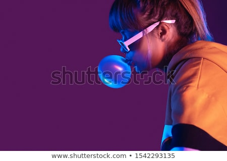 blond teenager girl blowing a bubble gum balloon stock photo © lopolo