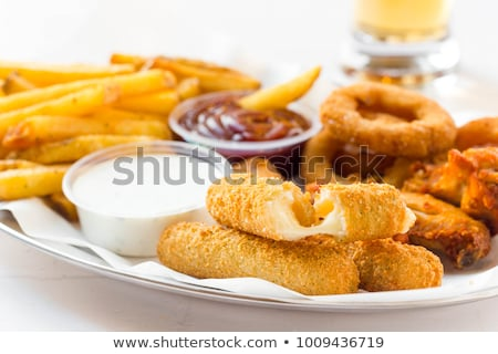 Sticks, fried onions and fried tomatoes with sauce Stock photo © boggy