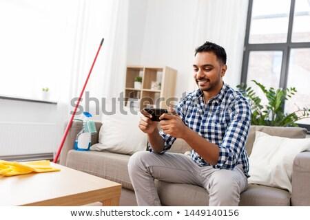 Człowiek gry gry smartphone czyszczenia domu Zdjęcia stock © dolgachov