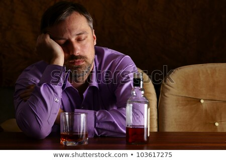 Portrait of young drunk man sitting with bottles stock photo © runzelkorn