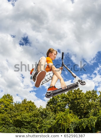 young boy going airborne with his scooter Stock photo © meinzahn