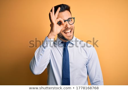 Businessman looking through finger's hole Stock photo © bmonteny