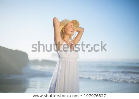 Beautiful smiling blonde in white sundress on the beach with sca Stock photo © wavebreak_media