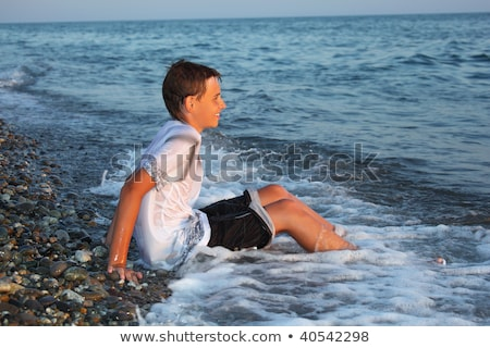 sitting teenager boy in wet clothes on stone seacoast Stock photo © Paha_L