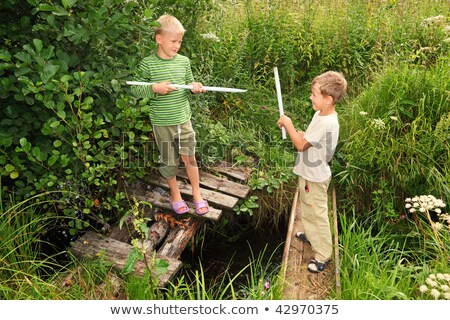 Two boys with sticks battling for fun on bridges over stream Stock photo © Paha_L
