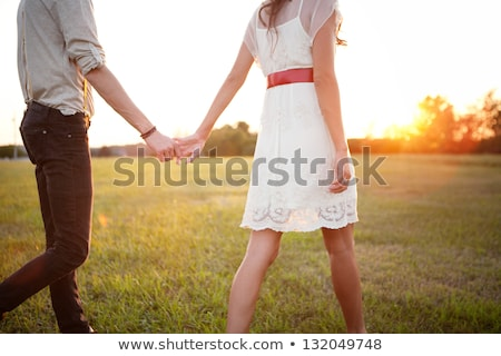 smiling beautiful couple holding hands at the beach stock photo © deandrobot
