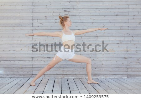 Yoga Warrior two II pose in wooden floor Stock photo © lunamarina