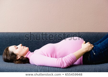 Pregnant woman laying on couch Stock photo © IS2