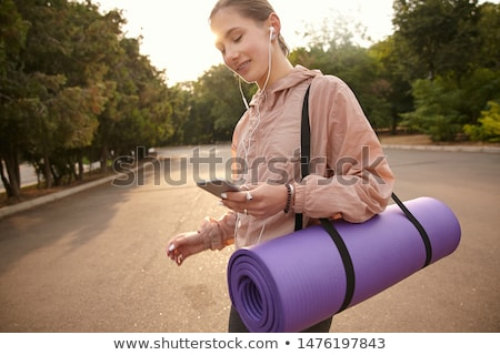 Fotó derűs fiatal nő 20-as évek sportruha hallgat Stock fotó © deandrobot